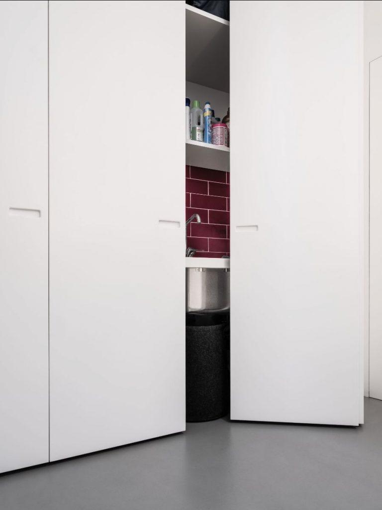 Perfekt versteckt: Im Treppenhaus befindet sich hinter raumhohen Falttüren ein kleiner Hauswirtschaftsraum für Trockner, Waschmaschine & Co.